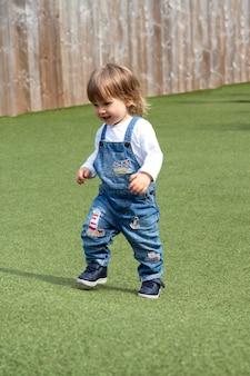 ロンドン、イギリス2021年7月22日-遊び場でクローバーで走っている幸せでアクティブな赤ちゃんの幼児の女の子。