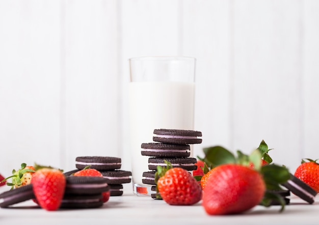 London, uk - may 03, 2018: oreo strawberry original cookies with fresh berries and glass of milk on wooden table.
