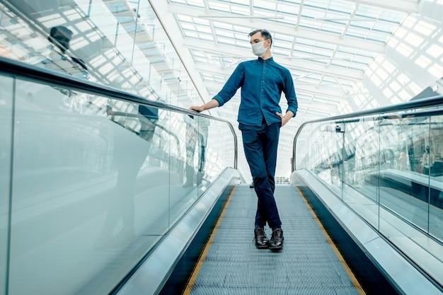 Одинокий мужчина в защитной маске стоит на ступенях эскалатора.