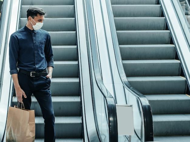 Одинокий мужчина в защитной маске стоит на ступенях эскалатора
