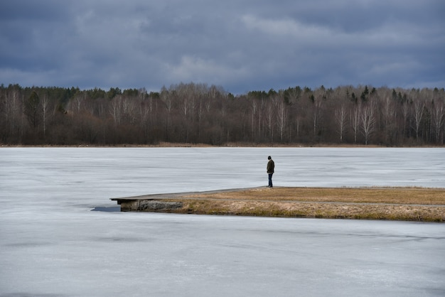 A lone man on the island looks at the frozen lake
