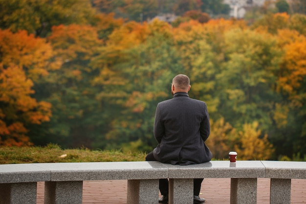 Lone man sitting on the stone bench and looking at nature. back view. autumn theme.