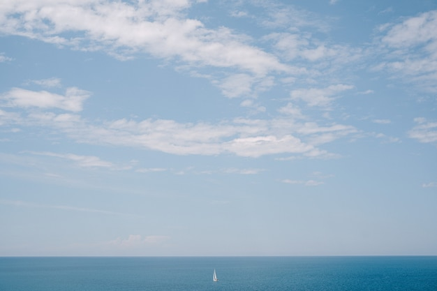 A lone sailboat floats in the distance on calm water ,blue sky. the concept of freedom and ease