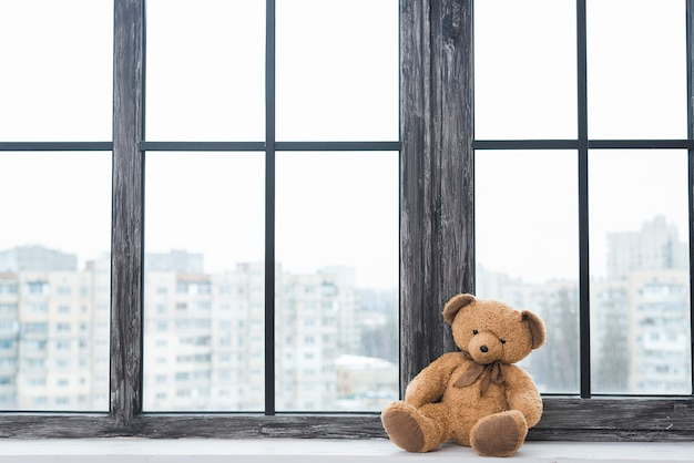 Lone teddy bear sitting near the closed window sill