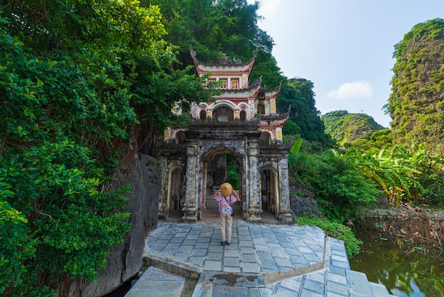 Lone tourist with traditional vietnamese hat at bich dong pagoda entrance gate, ninh binh vietnam, buddhist temple set amid jungle and karst mountain range. traveling alone, keep social distancing.