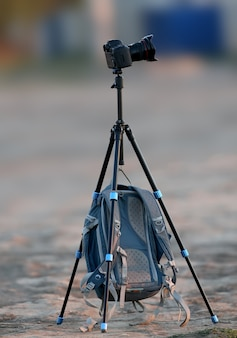 A lone tripod and a photographer's backpack hanging on it are photographed in the early morning on an empty site
