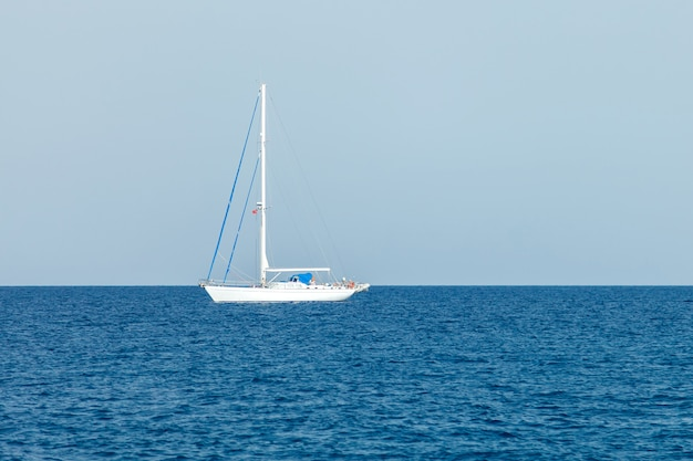A lone white yacht with lowered sails stands in the waters of the mediterranean sea