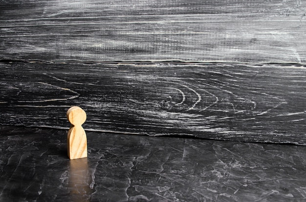 A lone wooden figure of a man stands on a gray background. a lonely man stands and looks.