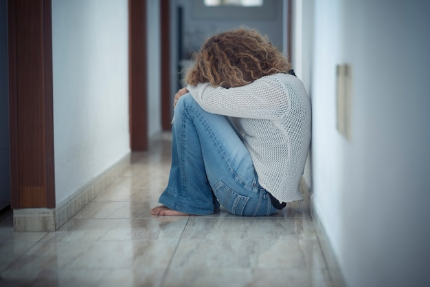 슬픈 여자와 외로움과 우울증 질병 개념은 혼자 집 바닥에 앉아 자신을 포옹-보호가 필요하고 여자와 아내 이미지에 대한 폭력