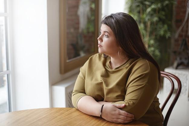 孤独の概念。カフェのテーブルに座って、孤独を感じ、一人で時間を過ごし、彼女の昼食を待って、悲しい物思いにふける表情で窓を通して見ている黒い髪の若いブルネットプラスサイズの女性