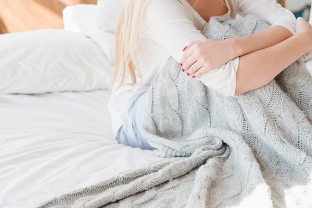 Loneliness isolation. winter melancholy. single woman with gray warm knitted blanket on bed.