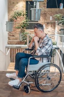 孤独。屋内の階段の前で物思いにふける車椅子の悲しい若い成人男性のプロフィール