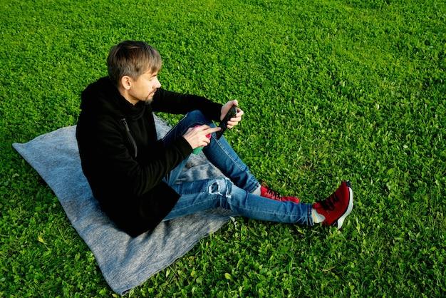 Одинокий, одинокий, одинокий мужчина средних лет пьет кофе в парке. концепция одиночества, социального дистанцирования и самоуничтожения. концепция психического здоровья, связь с природой
