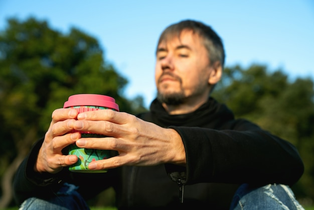 孤独な、一人で、公園でコーヒーを飲む一人の中年男性。孤独、社会的距離、自己嫌悪の概念。自然とつながるメンタルヘルスのコンセプト