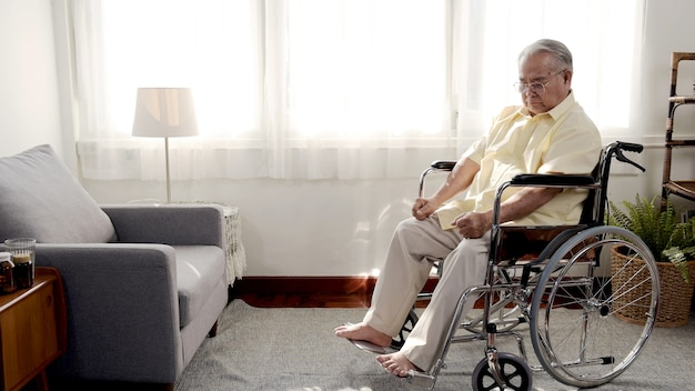 Lonely asian senior man was sick and sitting on wheelchair. retirement age lifestyle and stay at home alone.