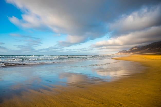 孤独なビーチは、曇り空の美しい山の表面で着色され、反射されます