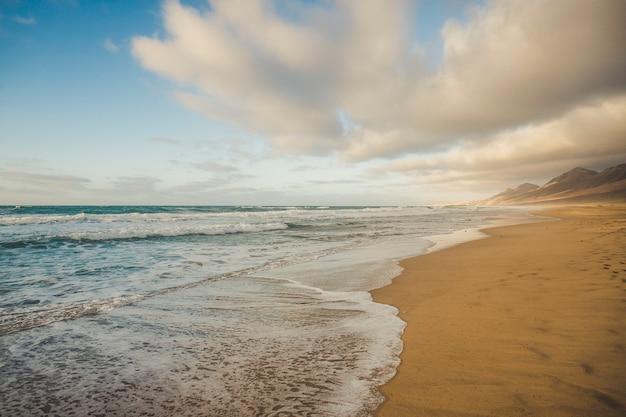 曇り空の美しい山の表面を持つ孤独なビーチ