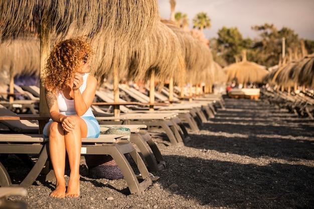 외로운 아름 다운 중 년 여자는 여름 휴가 하루에 해변에서 일광욕 침대에 앉아 기다리고 화창한 계절과 휴가 개념을 즐기고 찾고 있습니다. 칵테일 바