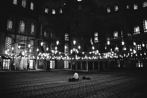 Lonely believers inside the blue mosque praying.