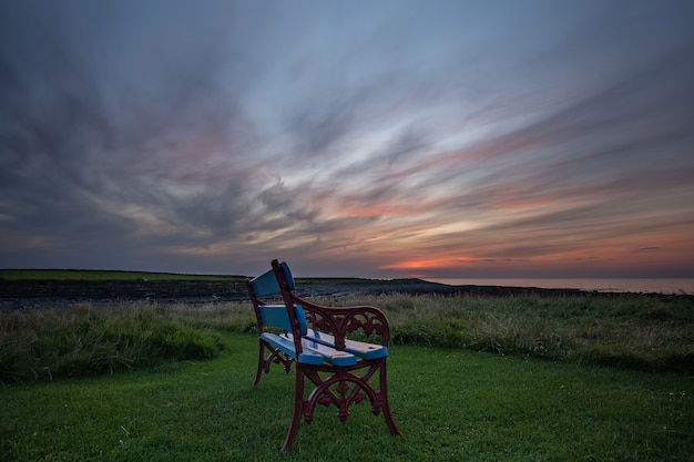 A lonely bench on sea coast at sunset