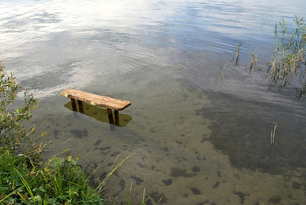 Lonely bench standing in the lake water