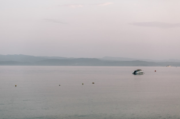 Barca solitaria galleggia nel mare sotto il cielo grigio