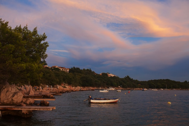 Одинокая лодка на закате с драматическим небом. заход солнца открытого моря с рыболовецким судном на горизонте.