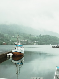 Lonely boat stands on the pierce covered with fog
