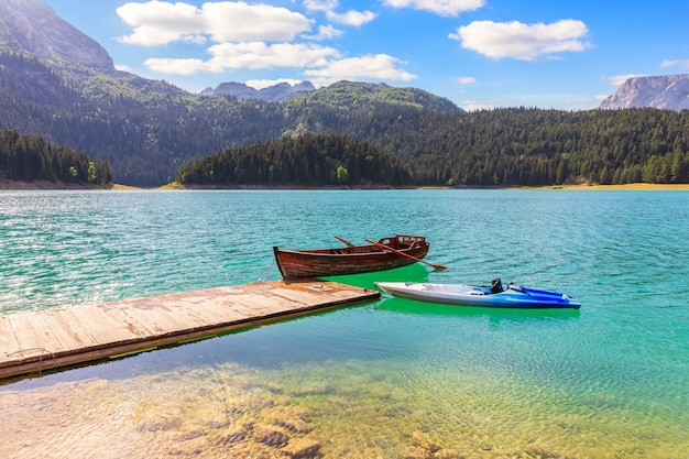 Lonely boats in the black lake on mount durmitor, montenegro.