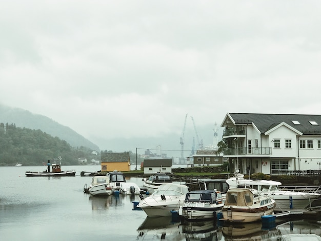 Lonely boats stand on the pierce covered with fog