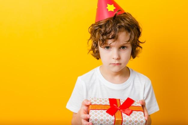 Одинокий мальчик в партийной кепке, держащей подарок.
