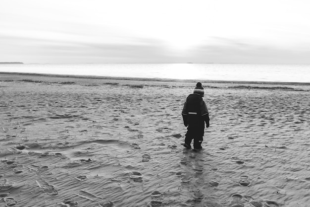 Одинокий мальчик на безлюдном пляже