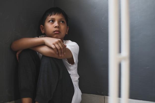 Одинокий мальчик грустит и сидит один дома