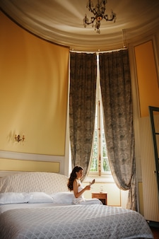 Lonely bride sits on the bed in a large hotel room
