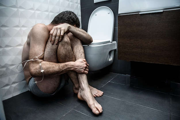 Одинокий сломанный мужчина с наркоманией сидит на полу в туалете в туалете