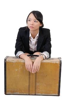 孤独なビジネスの女の子は、白い背景で隔離の古い旅行ケースと一緒に座っています。