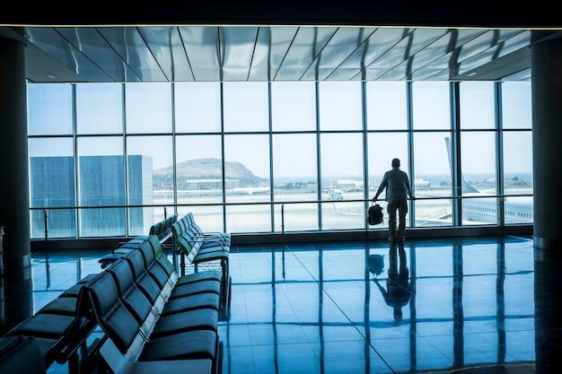 孤独なビジネスマンが旅行し、空港のゲートで待つ
