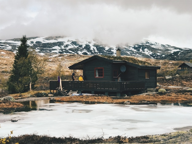Lonely cabin stands before the mountains covered with snow