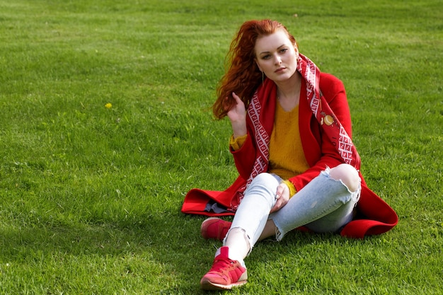 Lonely caucasian redhaired woman in a red coat and light jeans sits on green grass in the park during the day