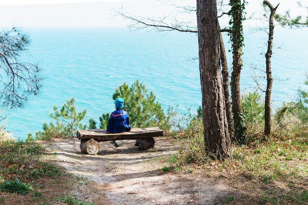A lonely child is resting on bench in the forest with a view of the sea.