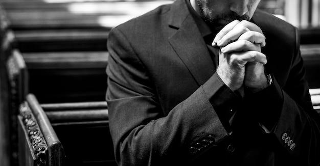 教会で祈る孤独なキリスト教徒の男性