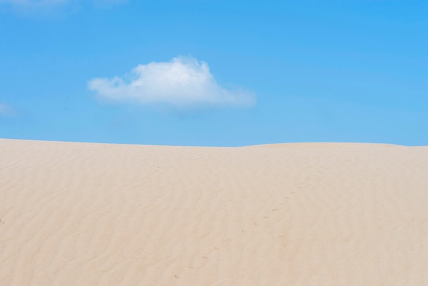Lonely cloud over a dessert dune against blue sky