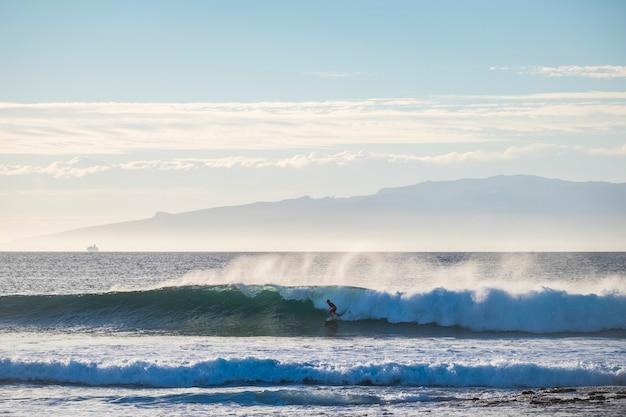 水平線の背景に船と島を持つ波の孤独なかわいいサーファー