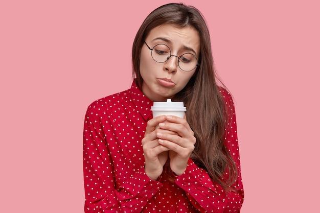 孤独な落胆した女性は下唇を財布に入れ、使い捨ての温かい飲み物を持って、悲しみを感じ、元気がない