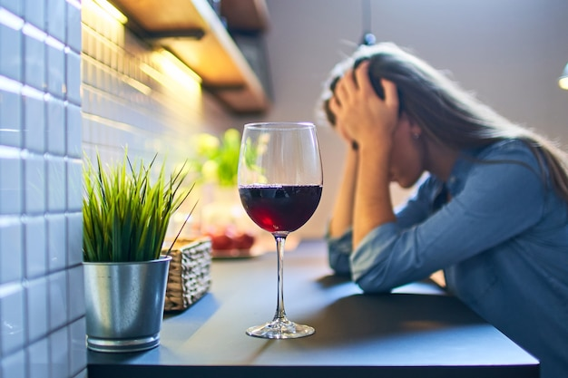 Lonely depressed drinking woman suffering from alcohol addiction abuse with red wine glass alone at home.