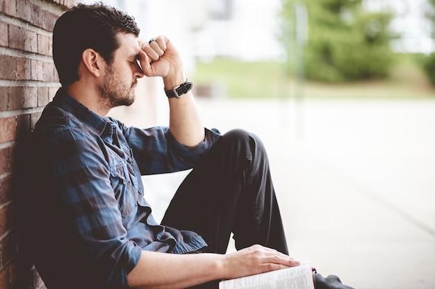 Одинокий депрессивный человек сидит возле кирпичной стены
