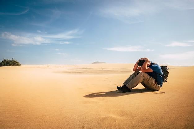 孤独な冒険のバックパッカーの男が砂漠の砂丘のどこにも一人で座っていない-人々が美しい世界を旅するための乾燥した気候変動の概念-極端なトレッキング休暇