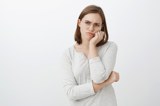 Одинокая недовольная и несчастная милая молодая женщина в очках с короткими каштановыми волосами, хмурясь и дуясь от печали, положив лицо на ладонь, равнодушно глядя на серую стену