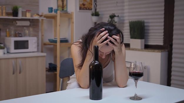 台所に座っている頭痛のある孤独な酔っぱらいの女性。片頭痛、うつ病、病気、不安感に苦しんでいる不幸な人は、アルコール依存症の問題を抱えているめまいの症状で疲れ果てています。