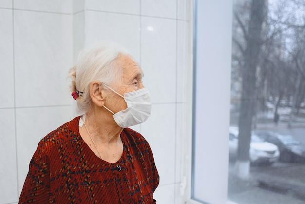 Одинокая пожилая женщина в медицинской маске, глядя в окно
